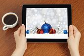 Hands hold tablet PC with Christmas composition