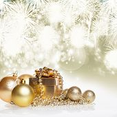 Golden gift box and christmas balls on bokeh background