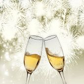 Toasting with two champagne glasses against holiday lights and fireworks