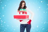 Pretty brunette posing and holding pile of gifts against blue vignette