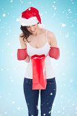 Happy brunette in boxing gloves looking in shopping bag against blue background with vignette
