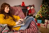 Redhead woman sitting on couch using laptop at christmas at home in the living room