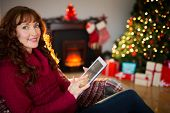 Smiling redhead using tablet at christmas at home in the living room