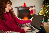 Smiling redhead using laptop at christmas at home in the living room