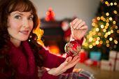 Smiling redhead holding red bauble at christmas at home in the living room