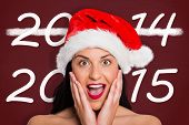 Surprised woman wearing santa hat against desk