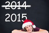 Festive brunette leaning on large poster against blackboard