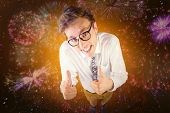 Young geeky businessman showing thumbs up against colourful fireworks exploding on black background