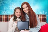 Mother and daughter showing tablet against blurred christmas background