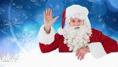 Portrait of santa claus waving against snowy landscape with fir trees