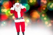 Portrait of happy santa claus posing against colourful glowing dots on black