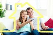 Charismatic man embracing his girlfriend while watching tv against house outline