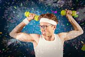 Geeky hipster posing in sportswear with dumbbells against white fireworks exploding on black background