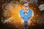 Geeky hipster looking confused at camera against colourful fireworks exploding on black background