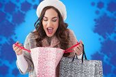 Surprised brunette looking in shopping bag against blurred snowflake design