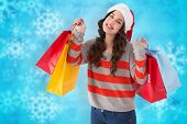 Cheerful brunette holding shopping bags against blurred christmas background