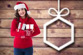 Festive brunette holding many gifts against blurred christmas decorations on wood