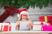 Festive blonde writing her christmas list against festive bow over wood