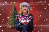 Festive blonde holding her hands out against blurred christmas tree background