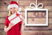 Festive blonde holding a gift against blurred christmas background