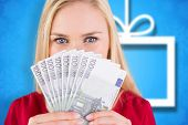 Pretty blonde in red dress showing her cash against blurred christmas background