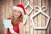 Smiling blonde in red dress wearing gloves and santa hat against blurred christmas decorations on wood