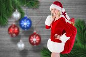 Festive blonde carrying sack of presents against christmas baubles hanging over wood
