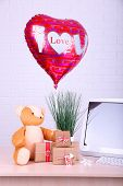 Teddy bear with present boxes, plant and love heart balloon on wooden  computer table, on the brick wall background