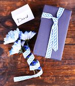 Happy Father's Day with gift box, ribbon, bouquet of flowers and greeting card on wooden background