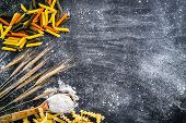 spikelets of wheat, pasta and spoon with flour  on a black  textured table