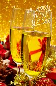 closeup of two glasses with champagne on a festive table full of gfits and the text happy new year written in the foreground