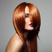 Beauty model with perfect long glossy red hair. Close-up portrait.