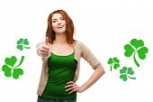 gestures, holidays, st. patricks day and people concept - happy teenager showing thumbs up  gesture over white background with green shamrock or clover