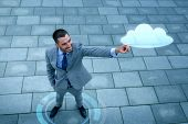 business, development, technology and people and concept - young smiling businessman pointing finger to cloud projection outdoors from top