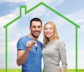love, home, people and family concept - smiling couple holding house key over green house and blue sky with grass background