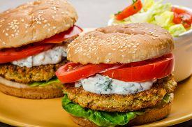 foto of veggie burger  - Vegetarian chickpea burger tomato and dip of herbs garlic and yogurt and salad with cherry tomatoes - JPG