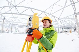 picture of geodesic  - female surveyor worker working with theodolite transit equipment at road construction site outdoors - JPG