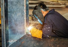 foto of tig  - worker welding steel construction by MIG welding process - JPG