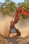 picture of track-hoe  - Large track hoe excavator moving rock and soil for fill for a new commercial development road construction project - JPG