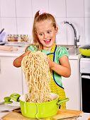 stock photo of pinafore  - Children  eating spaghetti at kitchen - JPG