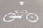 image of bike path  - Road mark on asphalt indicating reserved bike path, grey background, bicycle silhouette and straight arrow ** Note: Visible grain at 100%, best at smaller sizes - JPG