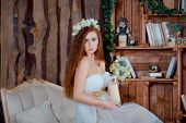 stock photo of rude  - Portrait of young beautiful rude girl with candle in rustic wood interior - JPG