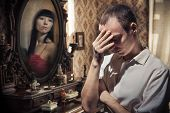 stock photo of grief  - Man in grief on the vintage mirror background - JPG