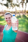 stock photo of bottle water  - female athlete holding a bottle of water in front of her with the focus on the water bottle - JPG