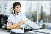 stock photo of showrooms  - Handsome young man standing besides car in showroom  - JPG