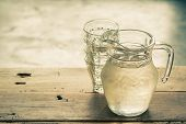 pic of pitcher  - Glass pitcher of water and glass on wooden table background vintage color tone - JPG