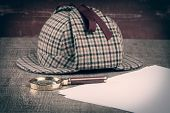 stock photo of sherlock holmes  - Deerstalker or Sherlock Hat and magnifying glass on Old Wooden table - JPG