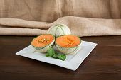 foto of cantaloupe  - Cantaloupe smal Melons on old wood table - JPG