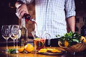 foto of sangria  - Man pouring red wine into a carafe - JPG