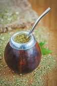 image of gaucho  - Latin traditional yerba mate tea in calabash with bombilla on wooden table background with green leaves - JPG